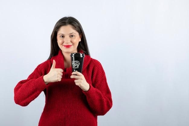 Ein junges frauenmodell im roten pullover mit einer tasse kaffee zeigt einen daumen nach oben
