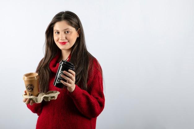 Ein junges frauenmodell im roten pullover mit zwei tassen kaffee