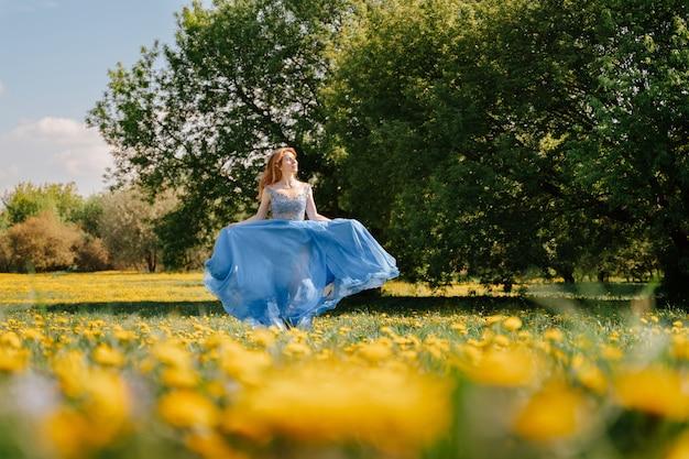 Ein junges fröhliches mädchen läuft in einem blauen langen kleid über ein feld mit gelben wiesenblumen, einen sommerrasen mit löwenzahn