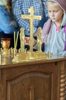 Ein junges gemeindemitglied zündet am altar in der kirche eine kerze an. gläubiges mädchen mit kerzen in der kirche