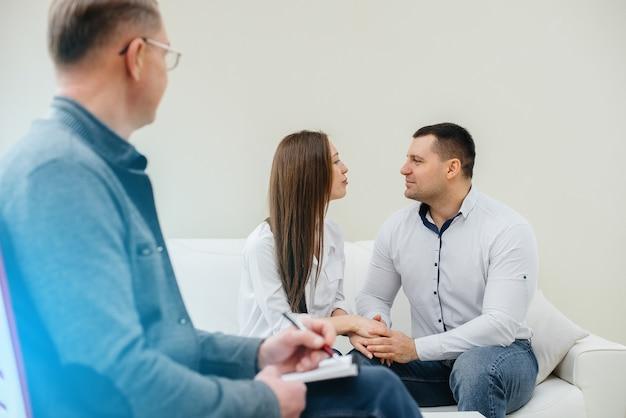 Ein junges glückliches ehepaar von männern und frauen spricht bei einer therapiesitzung mit einem psychologen. psychologie.