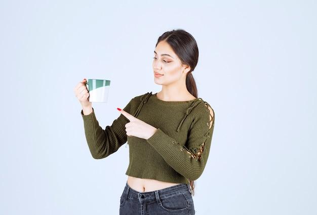 Ein junges hübsches frauenmodell, das auf eine tasse heißes getränk zeigt