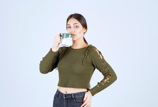 Ein junges hübsches frauenmodell, das aus einer tasse trinkt und die kamera betrachtet.