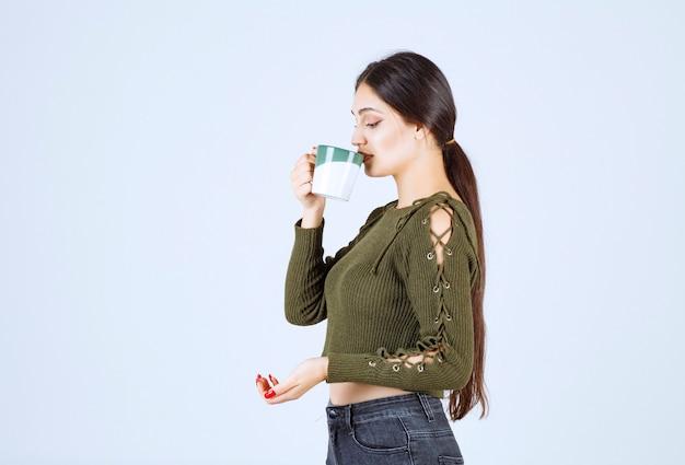Ein junges hübsches frauenmodell, das aus einer tasse trinkt