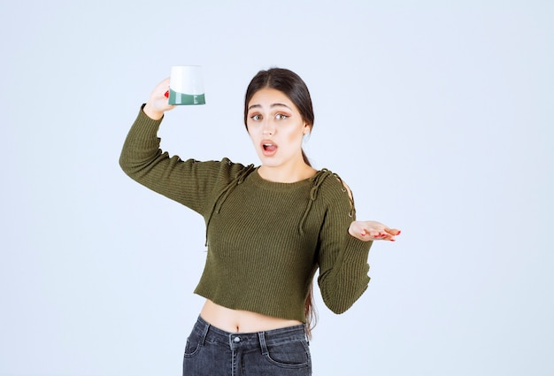 Ein junges hübsches frauenmodell, das eine leere tasse hält und in die kamera schaut