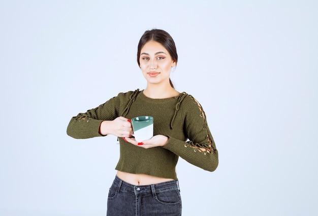 Ein junges hübsches frauenmodell, das eine tasse hält und in die kamera schaut