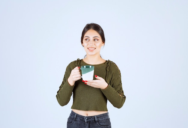 Ein junges hübsches frauenmodell, das eine tasse hält und wegschaut.