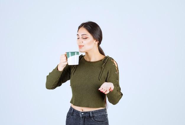 Ein junges hübsches frauenmodell, das eine tasse heißen tee genießt