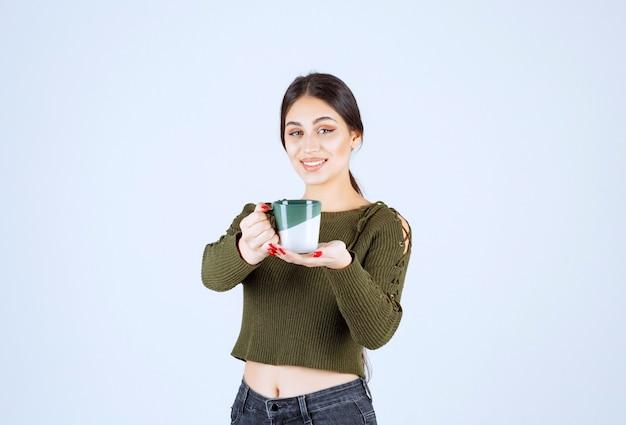 Ein junges hübsches frauenmodell, das eine tasse heißes getränk anbietet und die kamera betrachtet.