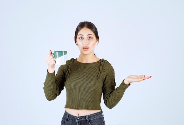 Ein junges hübsches frauenmodell, das eine tasse heißes getränk hält und die kamera betrachtet.