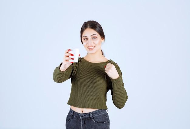 Ein junges hübsches frauenmodell, das einen plastikbecher mit heißem getränk anbietet.