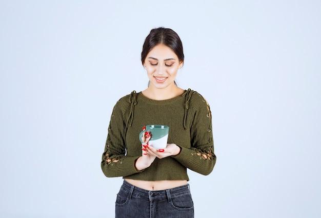 Ein junges hübsches frauenmodell im grünen pullover mit blick auf eine tasse