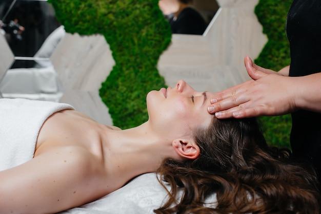 Ein junges hübsches mädchen genießt eine professionelle kopfmassage im spa