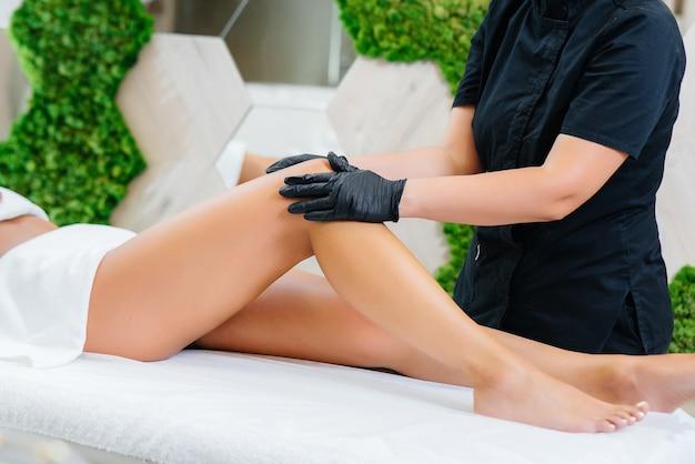 Ein junges hübsches mädchen genießt eine professionelle kosmetische massage im spa