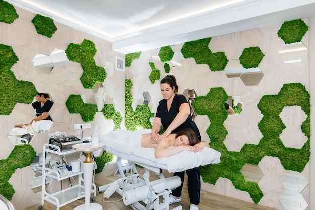 Ein junges hübsches mädchen genießt eine professionelle kosmetische massage im spa.