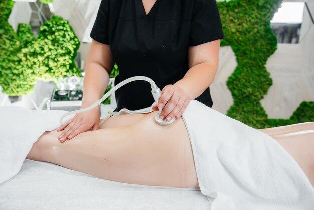 Ein junges hübsches mädchen genießt eine professionelle vakuummassage im spa. körperpflege. schönheitssalon.