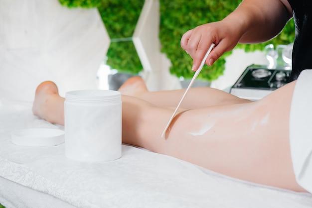Ein junges hübsches mädchen genießt im spa eine professionelle massage mit honig. körperpflege. schönheitssalon.