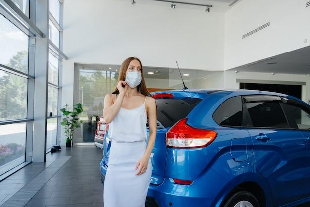 Ein junges hübsches mädchen inspiziert während der pandemie ein neues auto in einem autohaus in einer maske. der verkauf und kauf von autos in der zeit der pandämie.