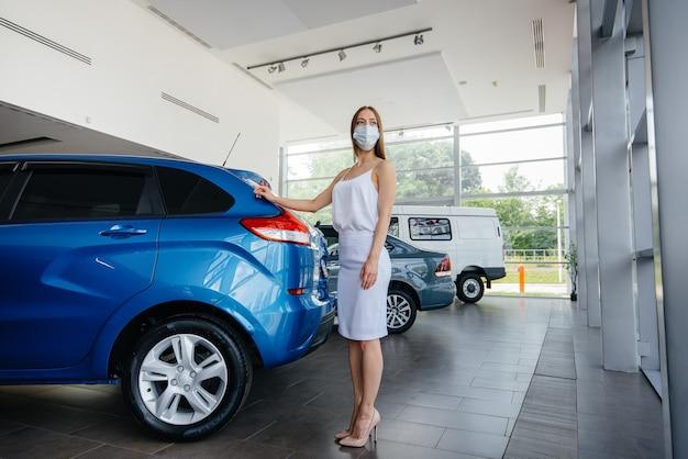 Ein junges hübsches mädchen inspiziert während der pandemie ein neues auto in einem autohaus in einer maske. der verkauf und kauf von autos in der zeit der pandemie.