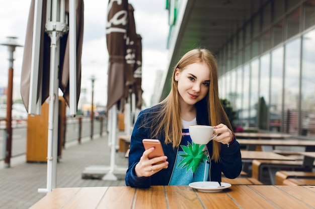 Ein junges hübsches mädchen mit langen haaren sitzt draußen im café am tisch. sie trägt eine blaue jacke. sie hält eine tasse kaffee und lächelt in die kamera.