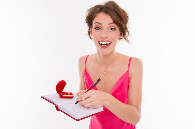 Ein junges hübsches mädchen mit welligem, braun gepatchtem haar, sauberer haut, glatten zähnen, einem hübschen lächeln in einem rosa trikot hält einen trainingsring in der hand und zeichnet etwas in einem notizbuch auf