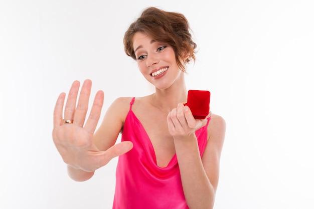 Ein junges hübsches mädchen mit welligem, braun gepatchtem haar, sauberer haut, glatten zähnen, einem hübschen lächeln in einem rosa trikot hält einen trainingsring in der hand, zeigt den verlobungsring an ihrer hand und freut sich
