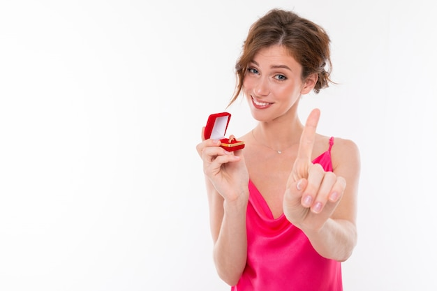 Ein junges, hübsches mädchen mit welligem, braun gepatchtem haar, sauberer haut, glatten zähnen, einem schönen lächeln in einem rosa trikot hält eine schachtel für einen trainingsring und rät, nicht zu eilen, um zu heiraten
