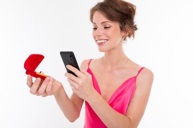 Ein junges hübsches mädchen mit welligem, braun gepatchtem haar, sauberer haut, glatten zähnen und einem hübschen lächeln in einem rosa trikot hält einen trainingsring in der hand und fotografiert ihn auf ihrem handy