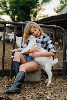 Ein junges hübsches mädchen posiert auf einer ranch mit ziegen und anderen tieren