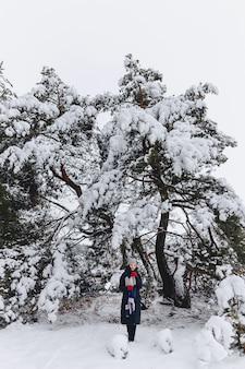 Ein junges, hübsches mädchen posiert unter einem großen schneebedeckten kiefernwald