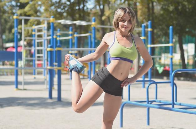 Ein junges kaukasisches athletenmädchen in einer hellgrünen sportkleidung, die aufwärmen tut