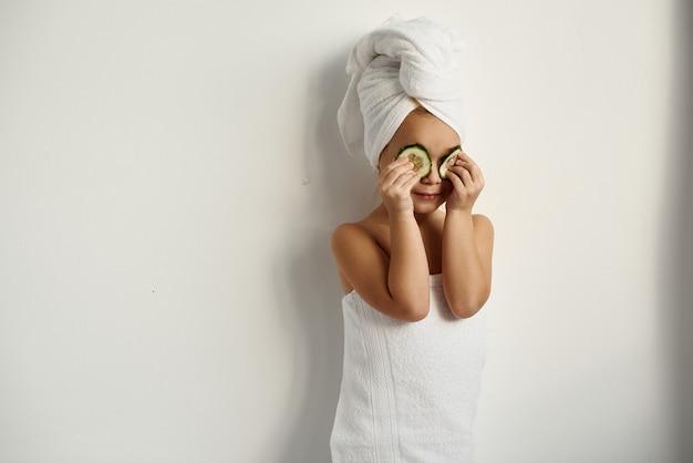 Ein junges kaukasisches kind mit eingewickeltem haar in weißen badetüchern, die gurkenstücke auf ihre augen auf einem weißen hintergrund anwenden
