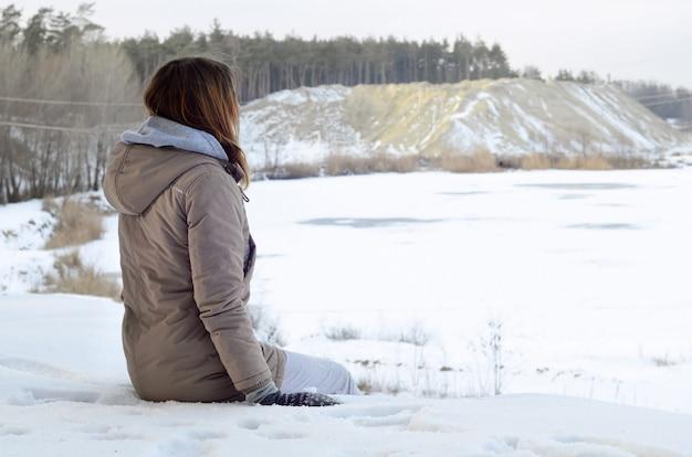 Ein junges kaukasisches mädchen in einem braunen mantel, der in den abstand auf der horizontlinie anstarrt