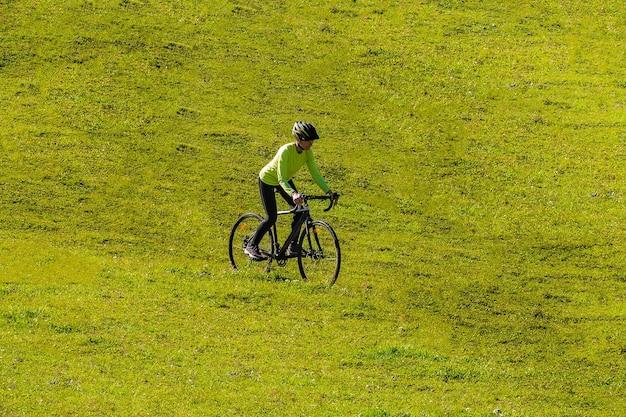 Ein junges lächelndes mädchen auf einem cyclocross-fahrrad fährt eine grüne helle wiese den hang hinunter