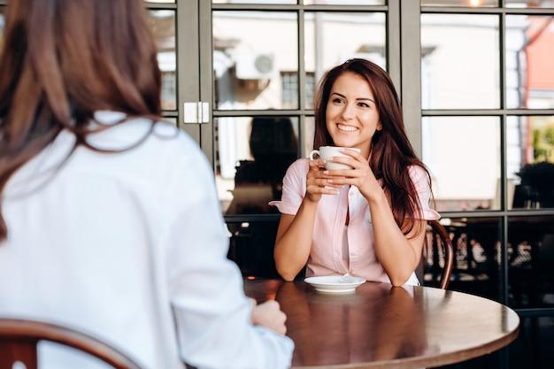 Ein junges, lächelndes mädchen hält eine tasse in den händen und kommuniziert mit ihrer freundin