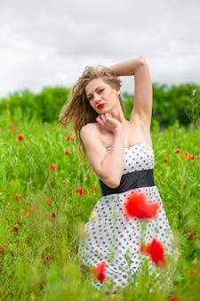 Ein junges langhaariges mädchen genießt an einem heißen sommertag die farben der natur auf einem blühenden mohnfeld.