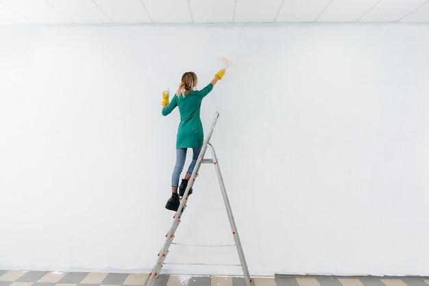 Ein junges mädchen auf einer trittleiter malt eine weiße wand mit einer walze. reparatur des innenraums.