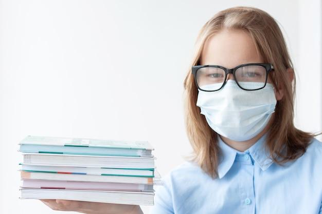 Ein junges mädchen, blond, in einem blauen hemd, das eine medizinische maske und eine brille auf weißem hintergrund trägt, schaut in die kamera und hält einen stapel lehrbücher in den händen.