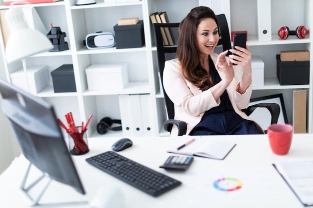 Ein junges mädchen, das an einem computertisch im büro sitzt, ein telefon anhält und ihren mund mit freude öffnet.