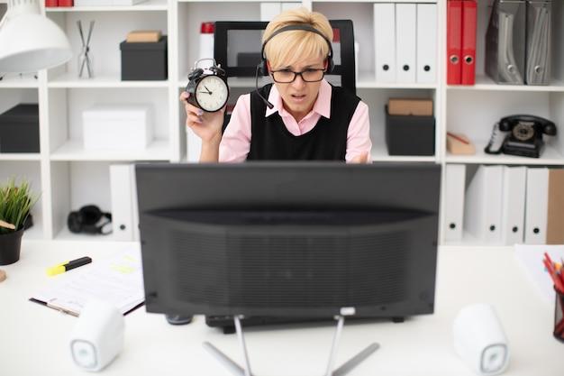 Ein junges mädchen, das an einem computertisch sitzt und einen wecker hält.