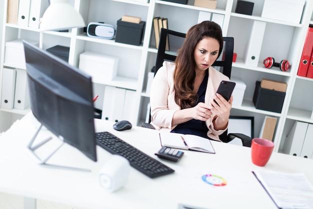 Ein junges mädchen, das an einem schreibtisch im büro sitzt, den telefonschirm betrachtet und erschrocken.