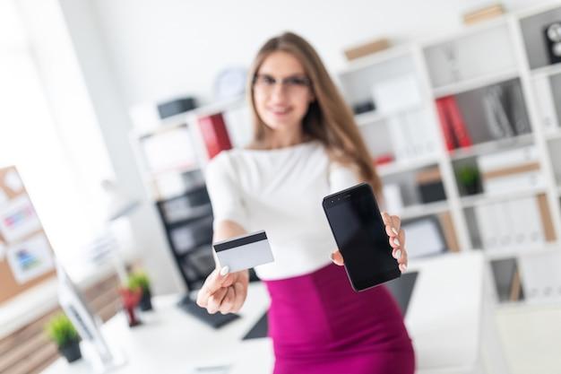 Ein junges mädchen, das an einem tisch sitzt und ein telefon und eine kreditkarte foto mit schärfentiefe, hervorgehobener fokus auf karte und telefon hält