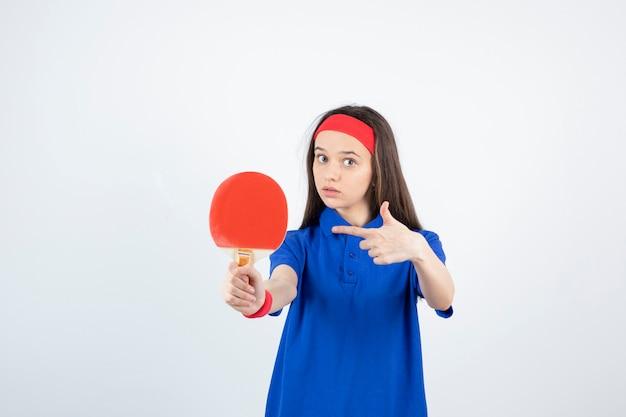 Ein junges mädchen, das auf tischtennisschläger auf einer weißen wand zeigt