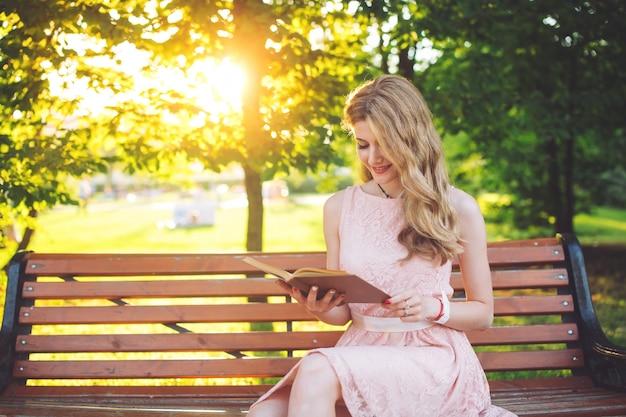 Ein junges mädchen, das ein buch sitzt auf einer bank am sonnenuntergang liest.