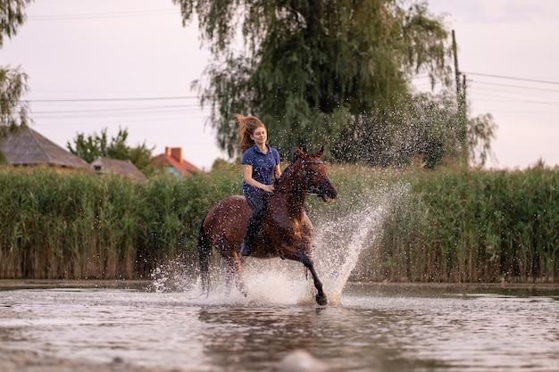 Ein junges mädchen, das ein pferd auf einen flachen see reitet.