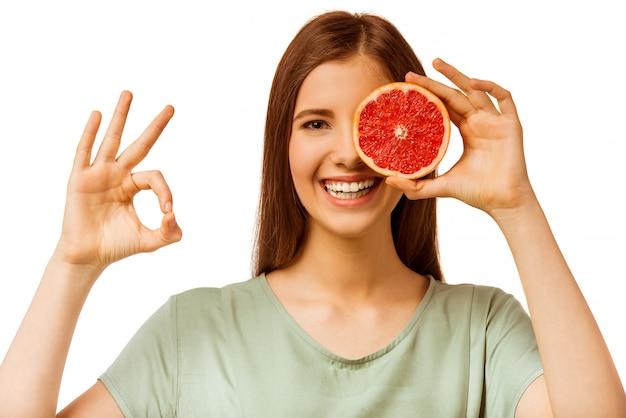 Ein junges mädchen, das eine orange anhält
