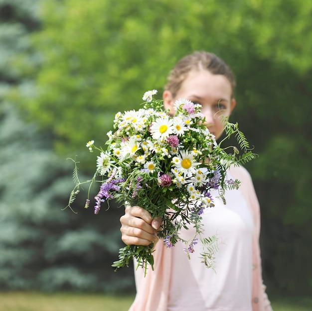 Ein junges mädchen, das einen blumenstrauß von wildflowers in den händen hält