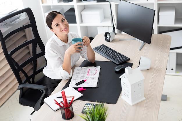 Ein junges mädchen, das im büro am computer sitzt und eine schale hält.
