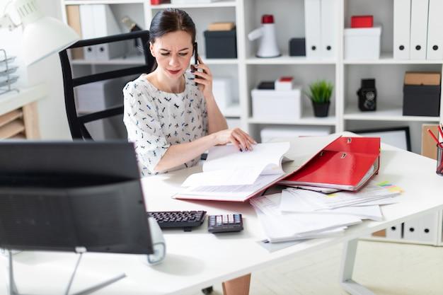 Ein junges mädchen, das im büro am computertisch sitzt, mit dokumenten arbeitet und am telefon spricht.