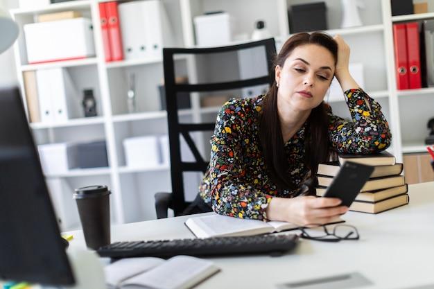 Ein junges mädchen, das im büro am computertisch sitzt und auf einem stapel büchern niederlegt.